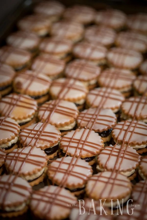 Plum Butter Cookies laid out on a baking sheet topped with icing and chocolate drizzle.