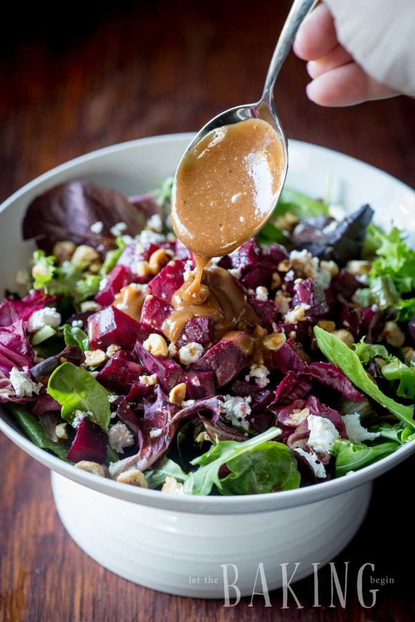 Salad topped with roasted hazelnuts, feta cheese, and vinaigrette being poured on the salad with a spoon in a white bowl.