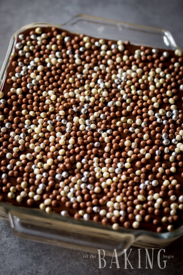 Top view of cake topped with pearls in a baking pan.
