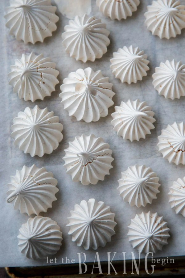 Top view of meringue cookies on a parchment lined baking sheet.