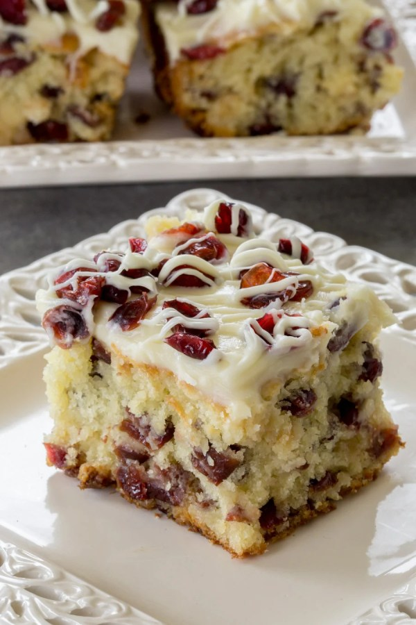 Cranberry Bliss Coffee Cake on a plate. Topped with cream cheese frosting and white chocolate.