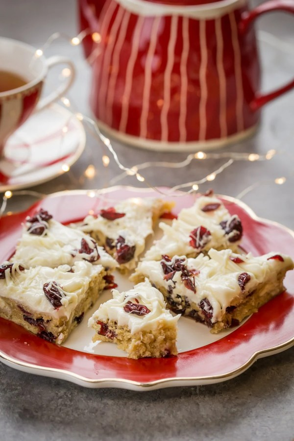 Cranberry Bliss Bar- Blondie base layer, which is generously speckled with white chocolate chunks and dried cranberries, then topped with orange flavored cream cheese frosting, sprinkled with more cranberries white chocolate drizzle.