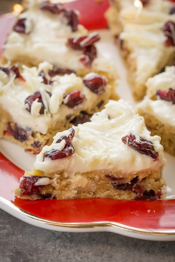 Cranberry Bliss Bars topped with dried cranberries on a plate.