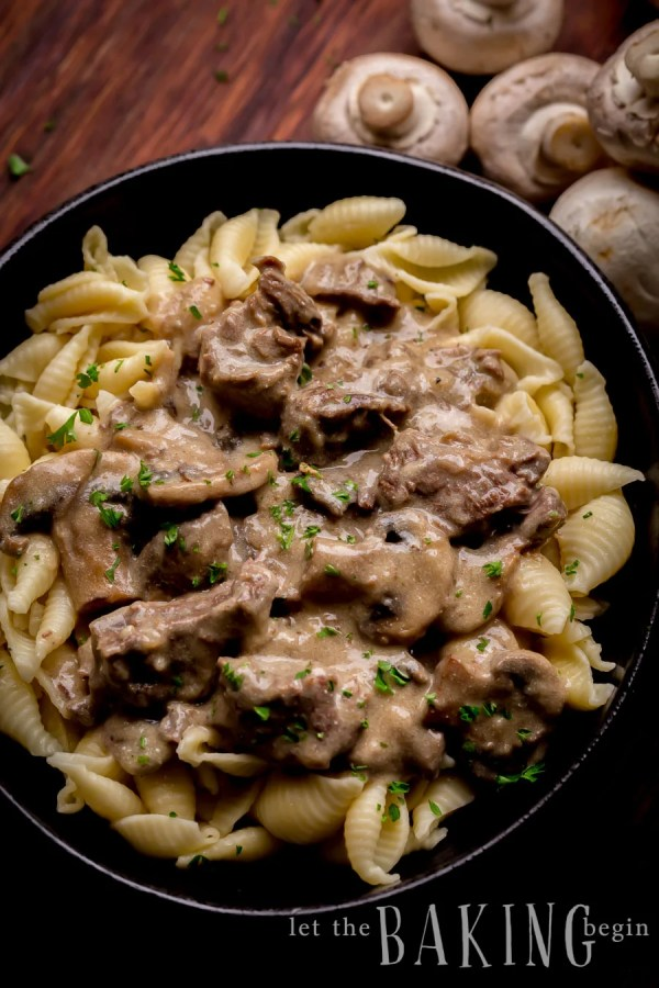 Beef stroganoff topped with fresh greens in a black bowl on a wooden table sided with mushrooms.