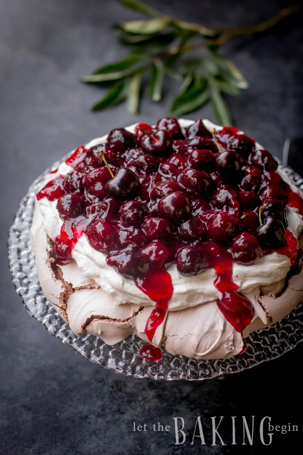 Assembled Cherry Chocolate Pavlova with the meringue disk, whipped cream and cherry sauce on top.