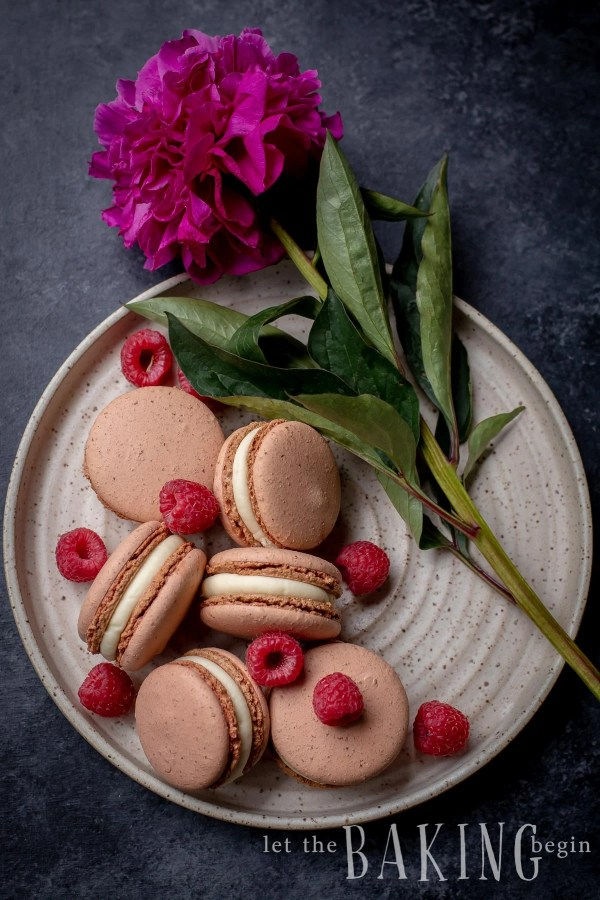 Macarons filled with White Chocolate Ganache and a fresh raspberry. These sweet meringue and chocolate cookies are so addicting!