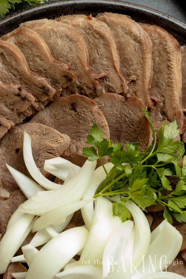 Beef recipes using cow tongue. Image of tongue sliced with herbs and onion.