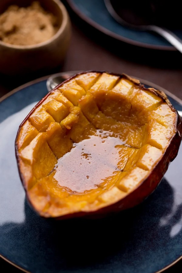 Half of Acorn Squash Baked with Brown Sugar and Butter on a plate, with lots of juice in the middle.