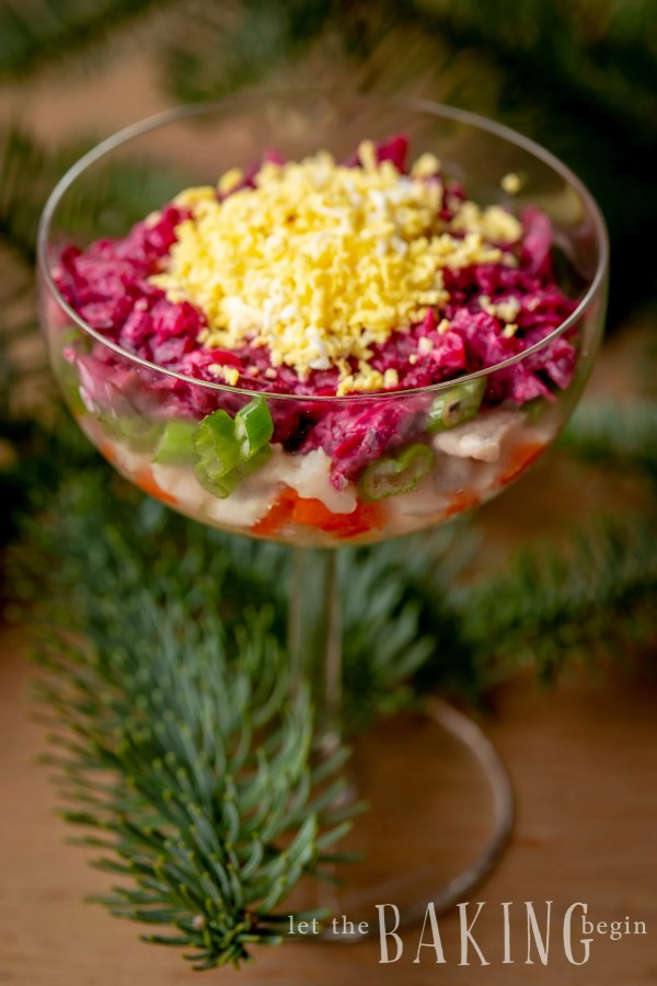 Layered beet salad without mayonnaise in a glass cup.