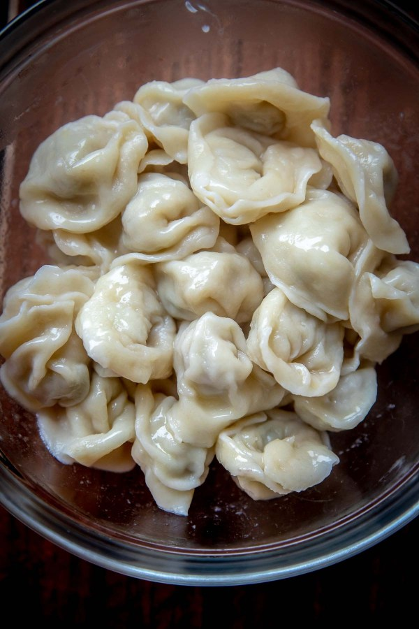 Chicken Pelmeni tossed with melted butter - tiny homemade dumplings made with soft and easy to make dough, then filled with juicy ground chicken filling.