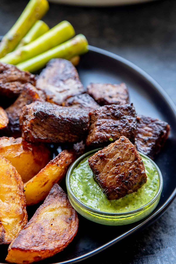 Steak bites with Asparagus, Roasted Potatoes on a plate, with one steak bite dipped in chimichurri sauce.