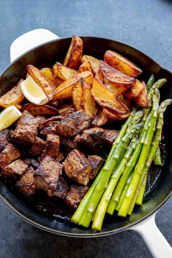 Steak bites, potatoes and asparagus in a skillet.