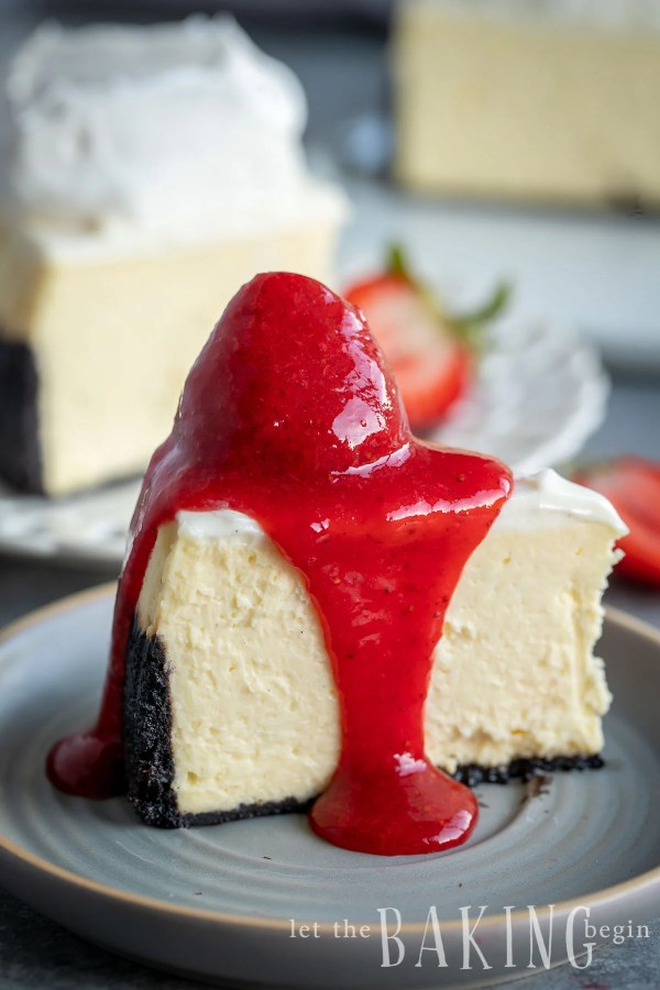 Slice of cheesecake with a whole strawberry and strawberry sauce on top.