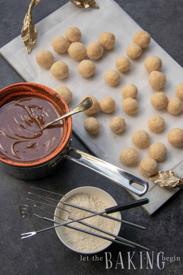 Coconut candy balls with bowl of melted chocolate next to them.