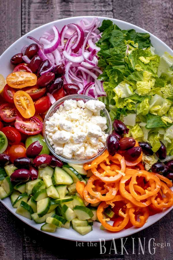 Deconstructed greek salad with lettuce, olives, bell peppers, cucumber, tomato, onion and feta cheese