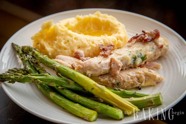 Plate with servings of a chicken bacon recipe, asparagu, and fluffy mashed potatoes.