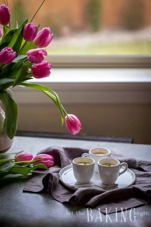 Panna cotta recipe in 3 white mugs on a table with pink tulips next to it
