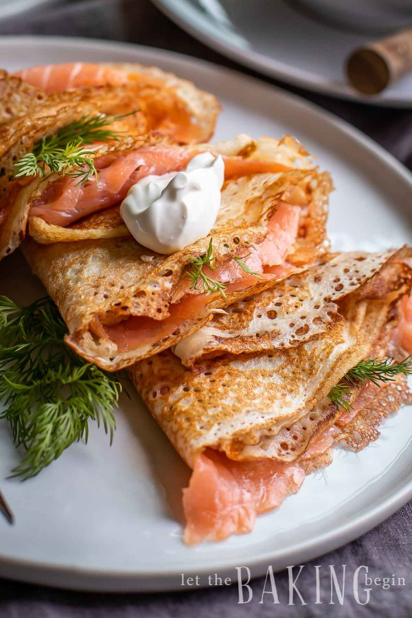 Russian blini recipe made with smoked salmon and topped with dill and sour cream