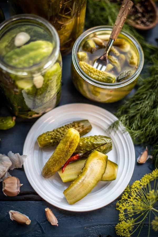 Homemade pickles next to a jar of a made pickle brine recipe.