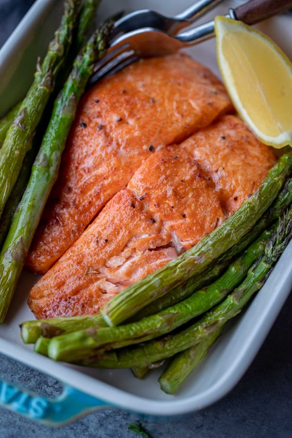 Two air fried salmon fillets surrounded by asparagus and a lemon wedge in a ceramic baking dish.