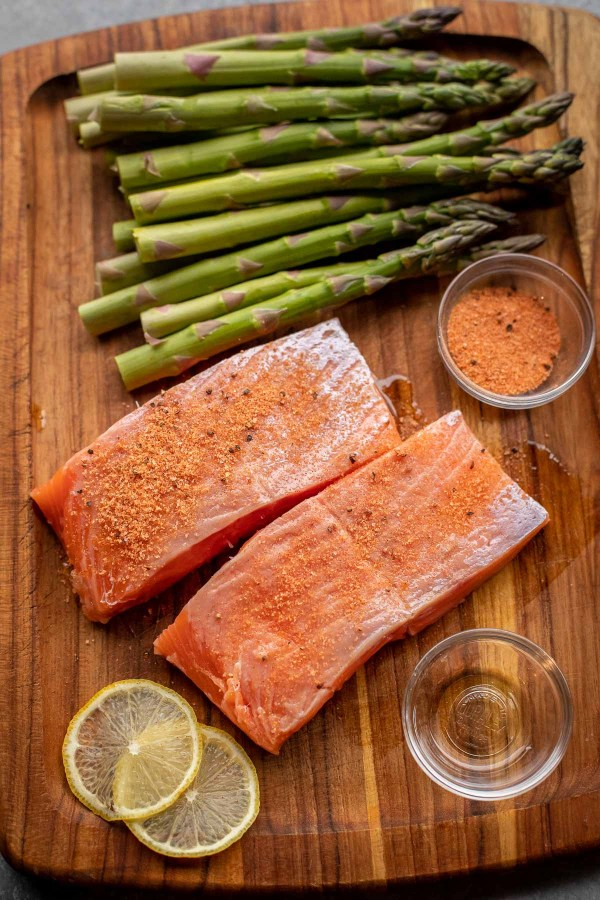 Ingredients for Air Fried Salmon and Asparagus laid out on a wooden cutting board.