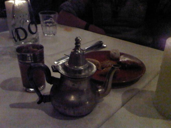 Moroccan pot of tea with mint leaves and a plate of sweets...