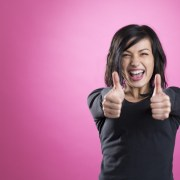 Excited girl giving thumbs up to show happiness