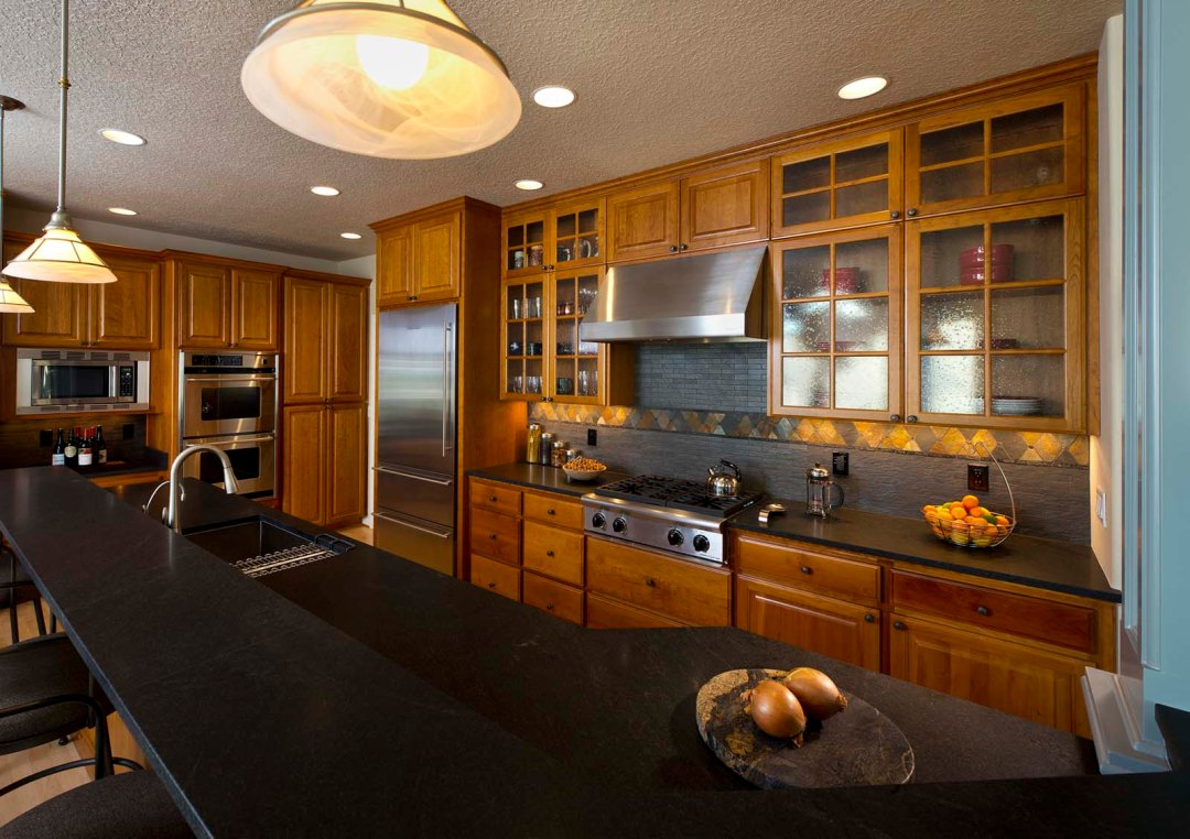 traditional home remodel with wood cabinets and black stone countertops