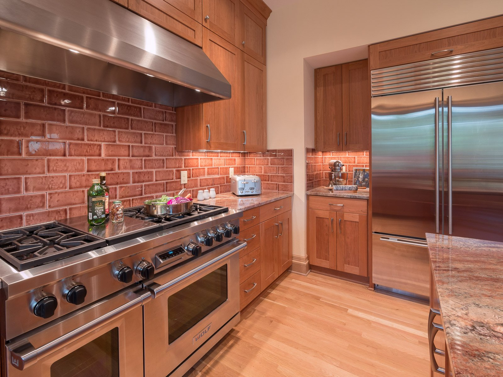 Contemporary Portland kitchen with stainless steel appliances and brick backsplash