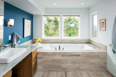 This renovated bathroom features a tub framed around reclaimed wood.