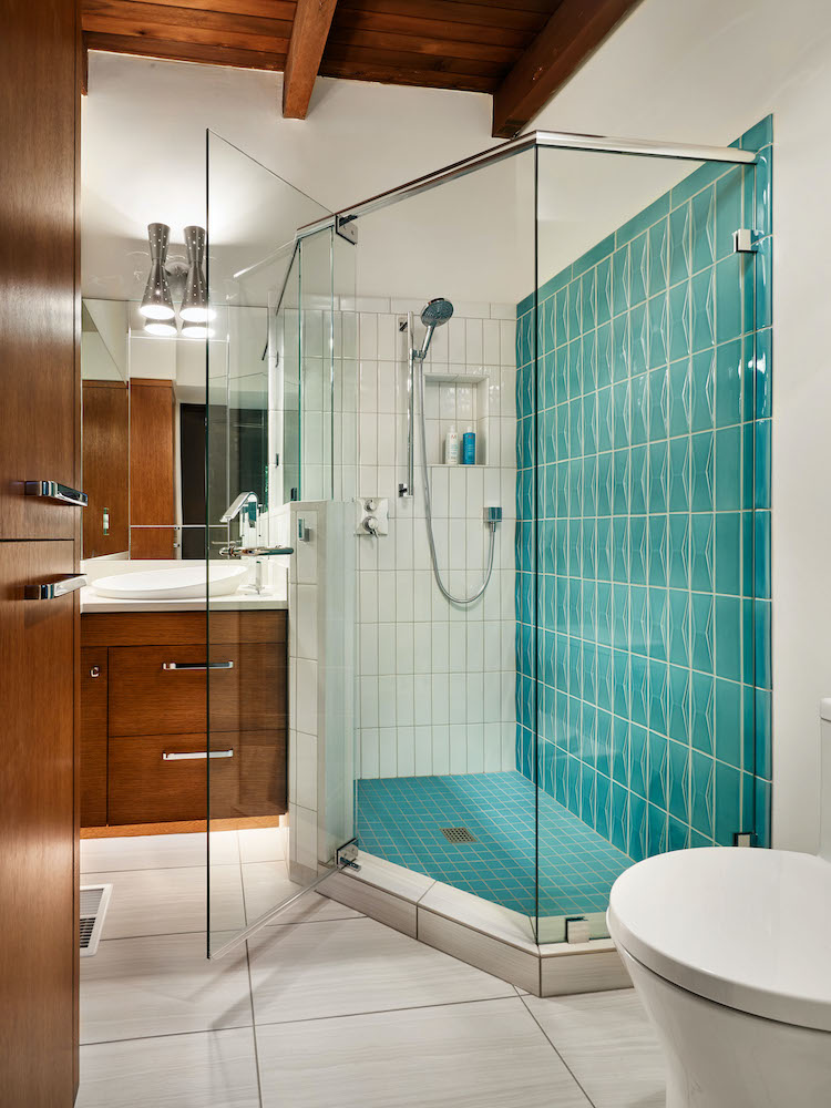 beautiful bathroom shower remodel with blue green tile white floors and mid century modern brown cabinets