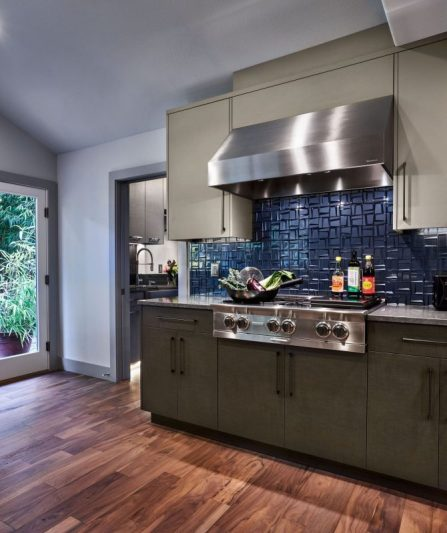 A kitchen counter with a stainless steel gas range and extractor fan and navy blue tiles