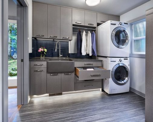 a laundry room with a stacked washer and dryer and grey cabinets and a farmhouse sink with clothes hanging