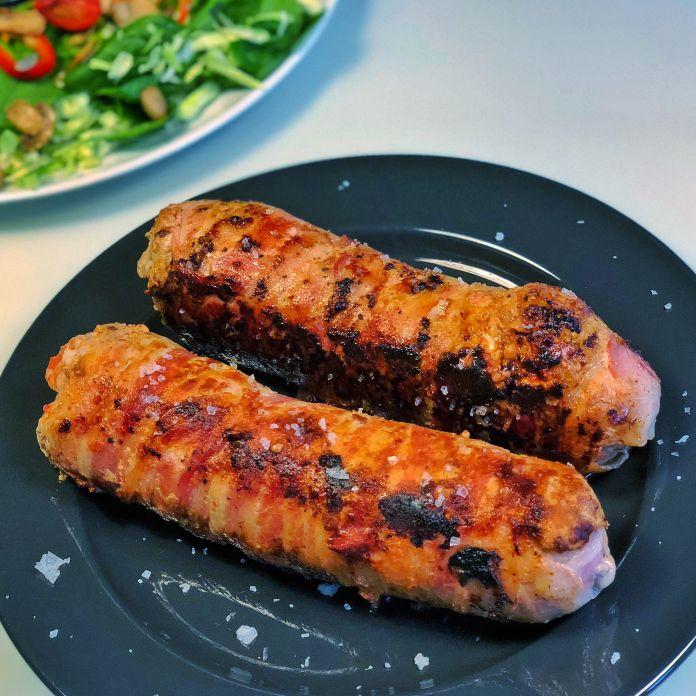 Baconsvøbte kødruller med pesto, hakkede oliven og cremet fetaost