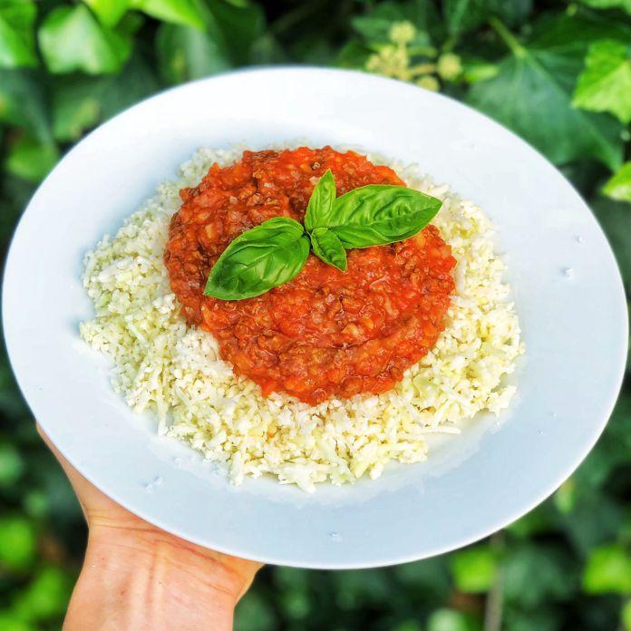 Smagfuld kødsovs med revet parmesanost og kogte blomkålsris
