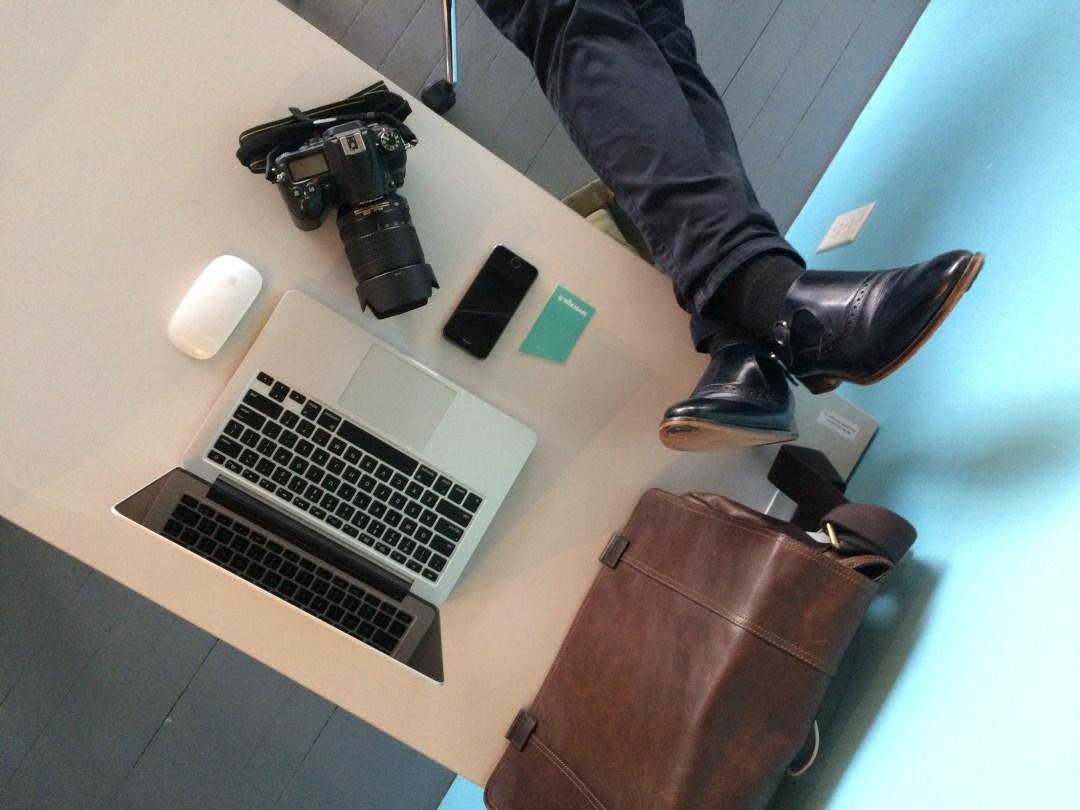 Man crossing his legs on top of desk