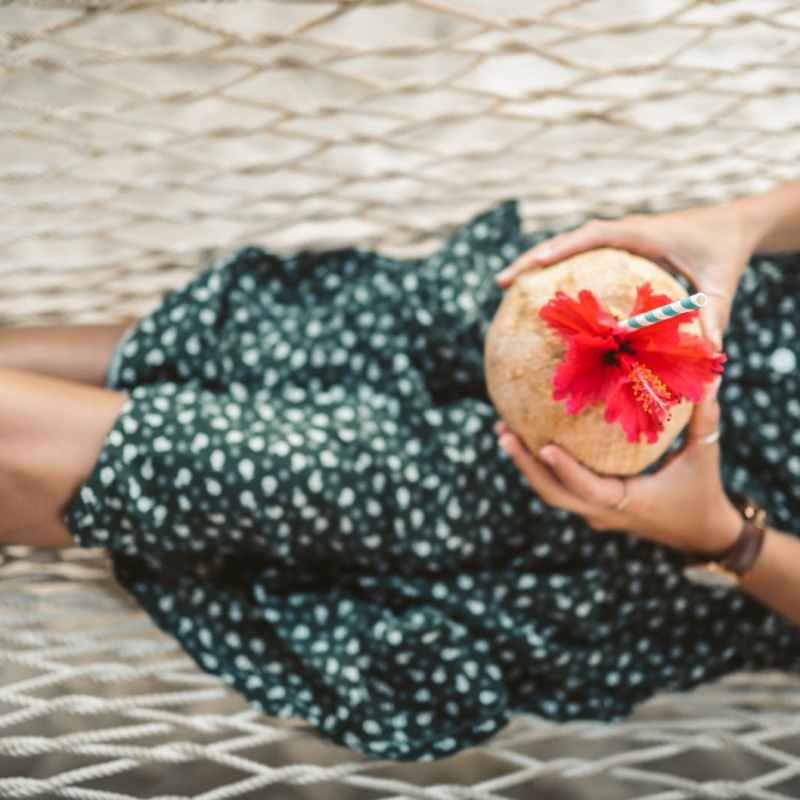 woman in green and white polka dot dress lying on a hammock with fresh coconut juice