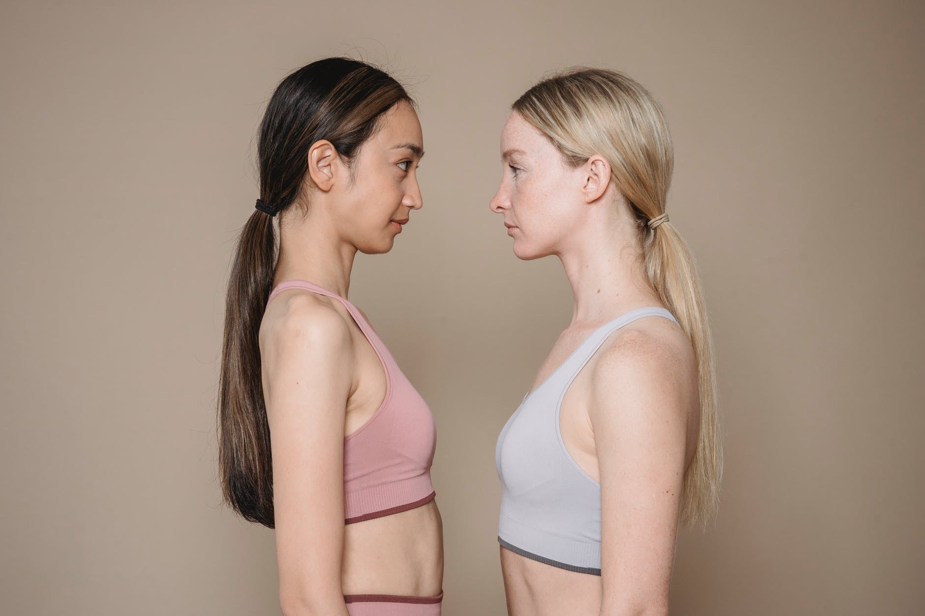 two women in sports bras looking at each other