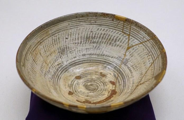 Lucrări de reparație (în partea dreaptă) prin metoda kintsugi cu lac auriu pe un bol de ceai de tipul hakeme Mishima, secolul al XVI-lea (Muzeul Etnologic din Berlin). Sursa: Wikipedia