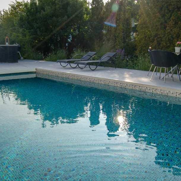 Skymning i trädgård med pool. Trädgårdsdesign Ulrika Levin.