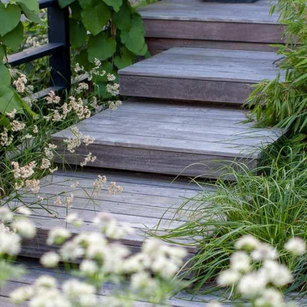 Trappa i trä med svävande trappsteg, omgivna av gräs och bambu. Ritad av Ulrika Levin, Levins Trädgård & Design.