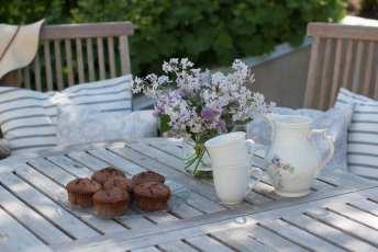 Chokladmuffins på fat och lila syrener i vas.