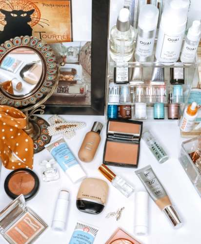 Vanity flatlay shelfie on a white desk with several beauty products: Dior Backstage foundation, First Aid Beauty Tinted Moisturizer, IT Cosmetics CC Cream, Milk Flex Foundation Stick, Milk Hydrogrip primer, Mac Skinfinish highlighter, Smashbox Vlada Highlighter, Sunday Forever Coconut Perfume, Marc Jacobs Daisy, Ouai hair care, Function of Beauty Serum.