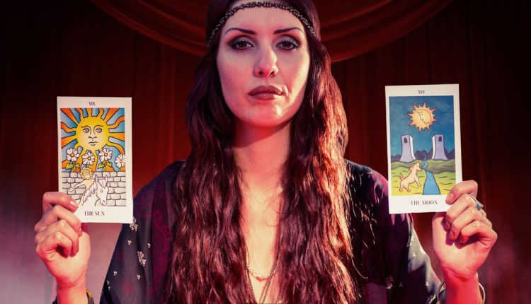 Portrait of fortune teller woman showing tarot cards  against large hanging curtain