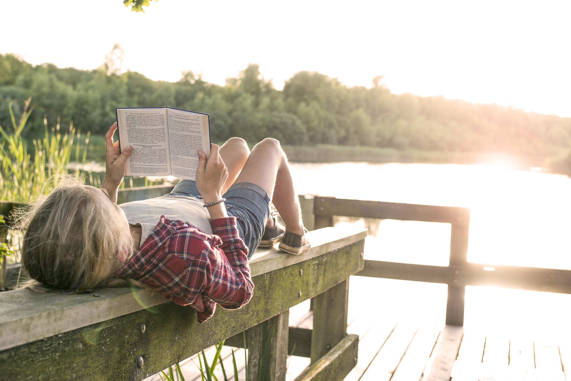 Young girl reading a book while lying on her back on a wooden beam at a wooden dock at the lake.