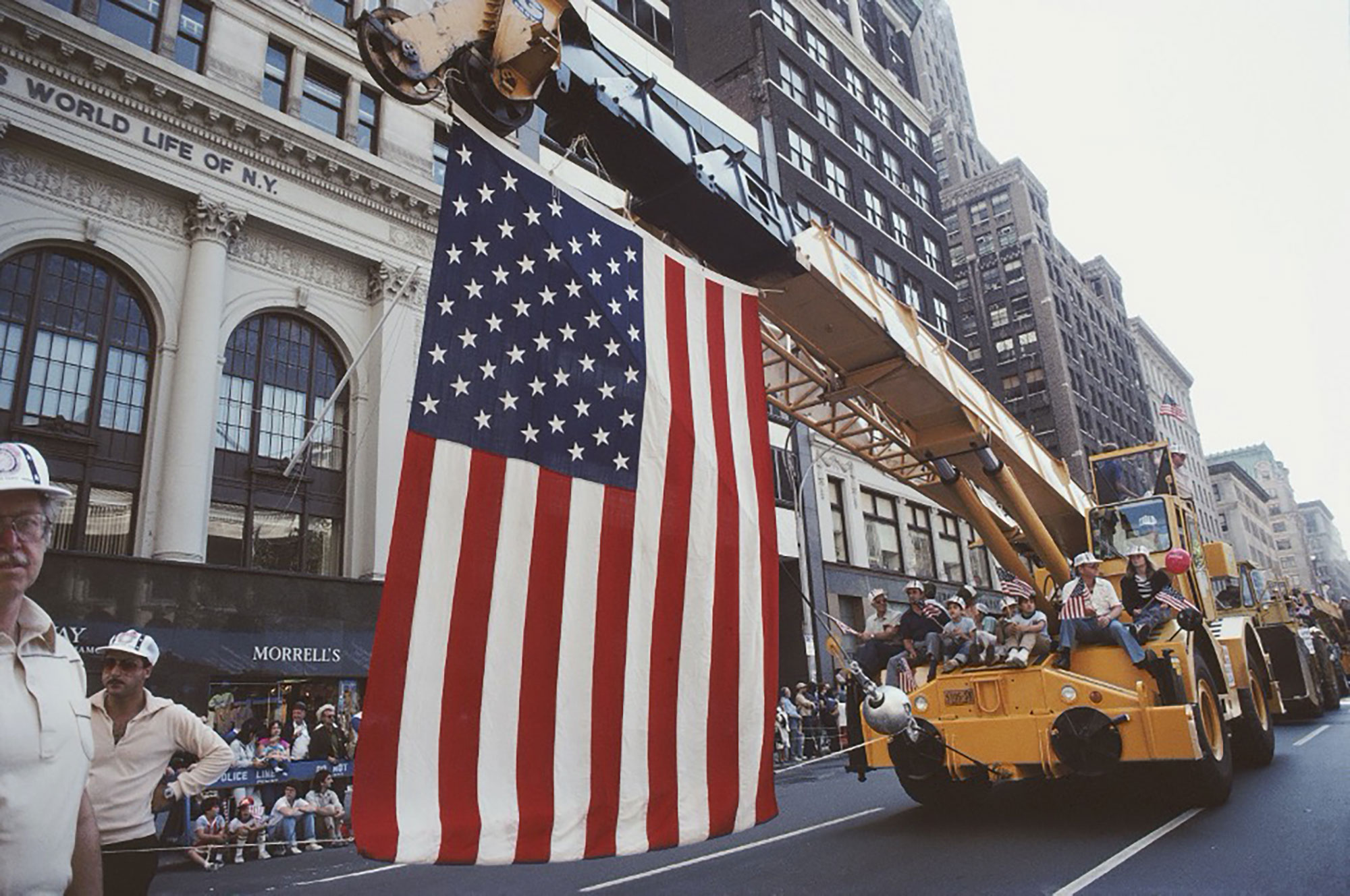 A large American flag is suspended from a crane in a Labor Day parade in New York City, 1982. Barbara Alper — Getty Images