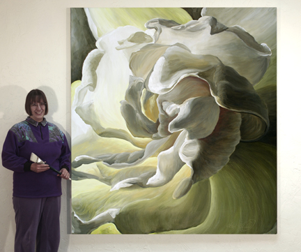 The artist stands beside a large flower painting