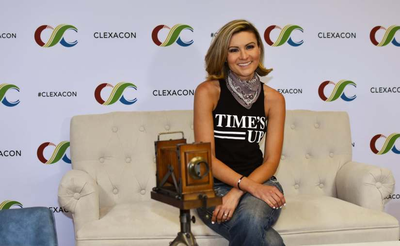 """Haviland Stillwell at ClexaCon 2019 in a """"Times Up"""" shirt, sitting on a couch.  (Photo by Mika Epstein/LezWatch.TV)"""