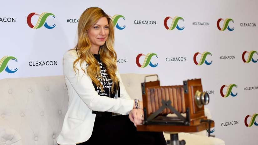 Jes Macallan at ClexaCon 2019 sitting on a couch, smiling. (Photo by Mika Epstein/LezWatch.TV)
