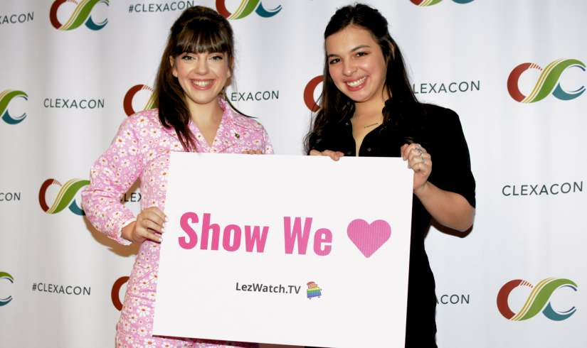 """Sheridan Pierce and Isabella Gomez at ClexaCon 2019 holding  a sign that says """"Show We Love"""" - LezWatch.TV  (Photo by Tracy Levesque/LezWatch.TV)"""